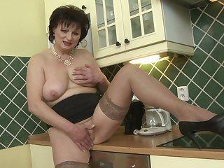 Short haired brunette MILF Dalia masturbates in the kitchen